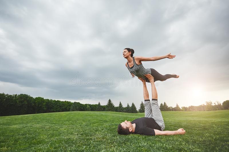 Healthy lifestyle. Strong man lying on grass and balancing woman on his feet. Young couple practising acro yoga in royalty free stock photos