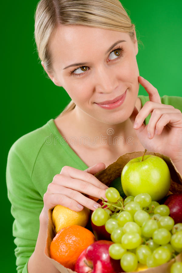Healthy lifestyle - thoughtful woman with fruit. Shopping paper bag on green background royalty free stock photo