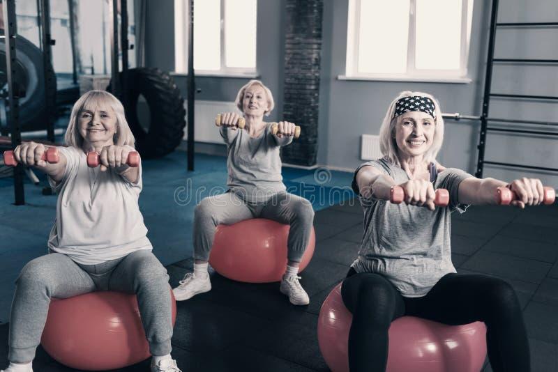Three elderly ladies holding dumbbells while sitting on exercise balls royalty free stock photos