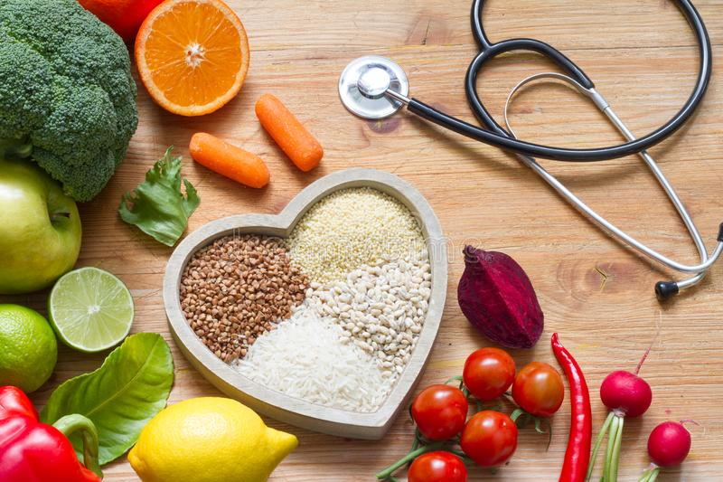 Healthy lifestyle with vegetarian food in heart and stethoscope alternative medicine concept. Closeup stock images