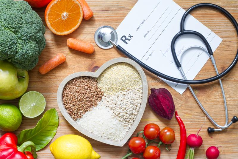 Healthy lifestyle with vegetarian food in heart and stethoscope alternative medicine concept. Closeup stock photos
