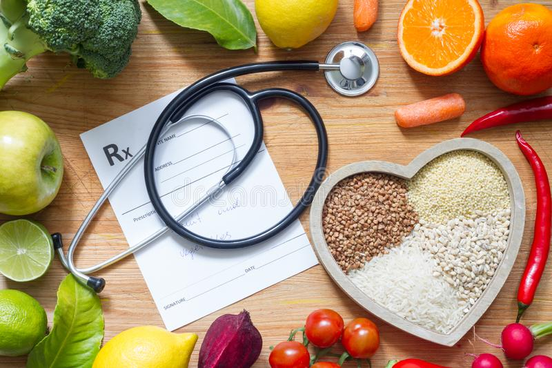 Healthy lifestyle with vegetarian food in heart and stethoscope alternative medicine concept stock image