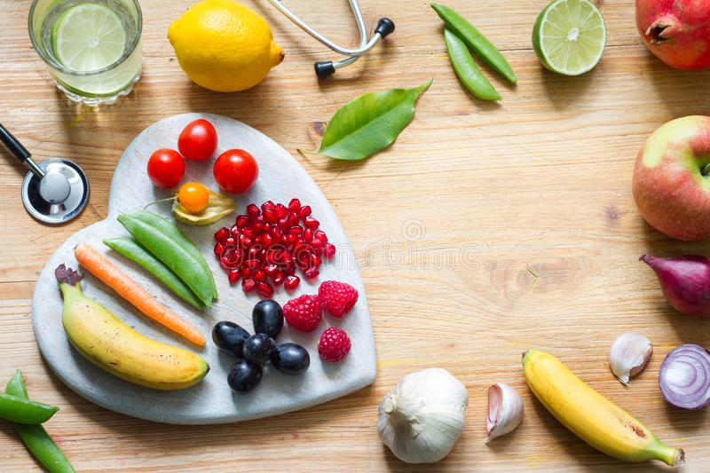 Healthy lifestyle vegetarian food in heart and stethoscope with water alternative medicine background concept. Closeup stock photos