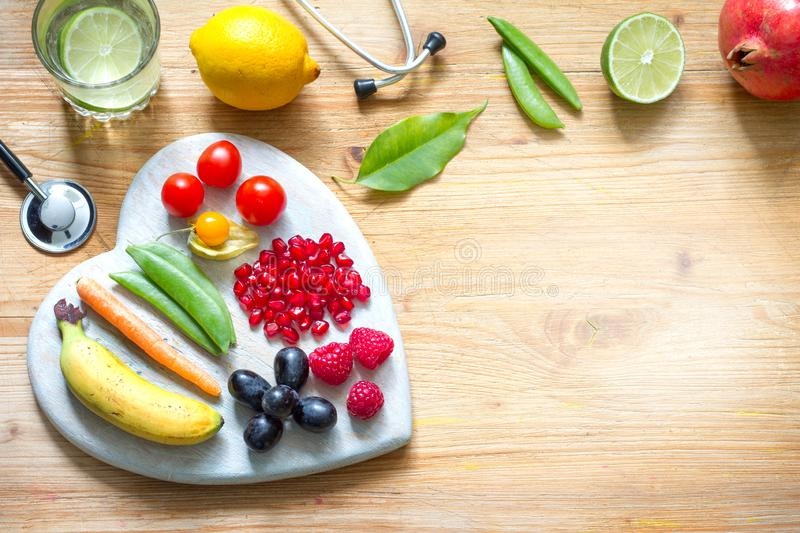 Healthy lifestyle vegetarian food in heart and stethoscope with water alternative medicine background concept. Closeup stock images