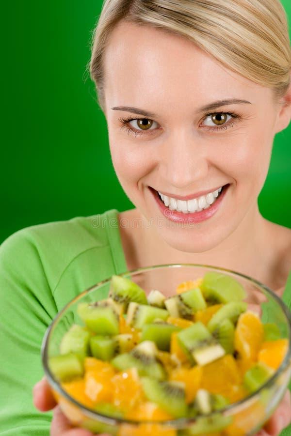 Healthy lifestyle - woman holding fruit salad bowl stock photo