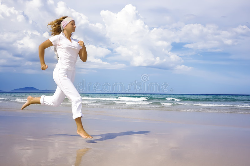 Healthy lifestyle. Woman running near the ocean stock photo