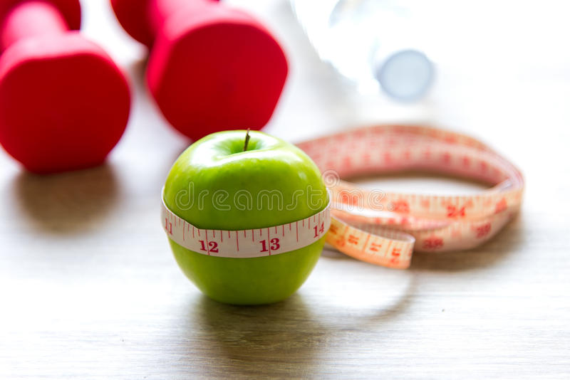 Healthy lifestyle for women diet with sport equipment, sneakers, measuring tape, fruit healthy green apples and bottle of water on. Wooden, select focus stock image