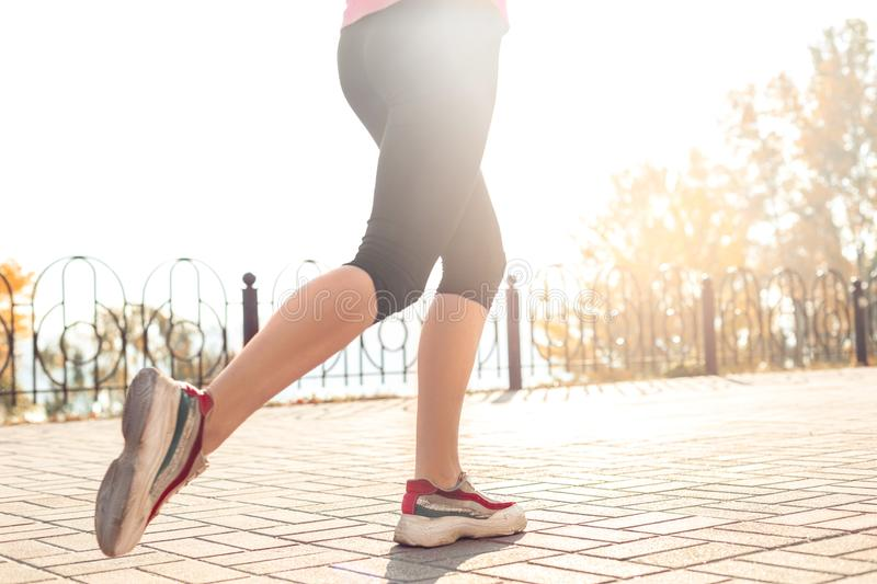 Healthy Lifestyle. Young woman jogging outdoors autumn season feet close-up. Young woman maintaining healthy lifestyle jogging outdoors autumn season feet in stock photography