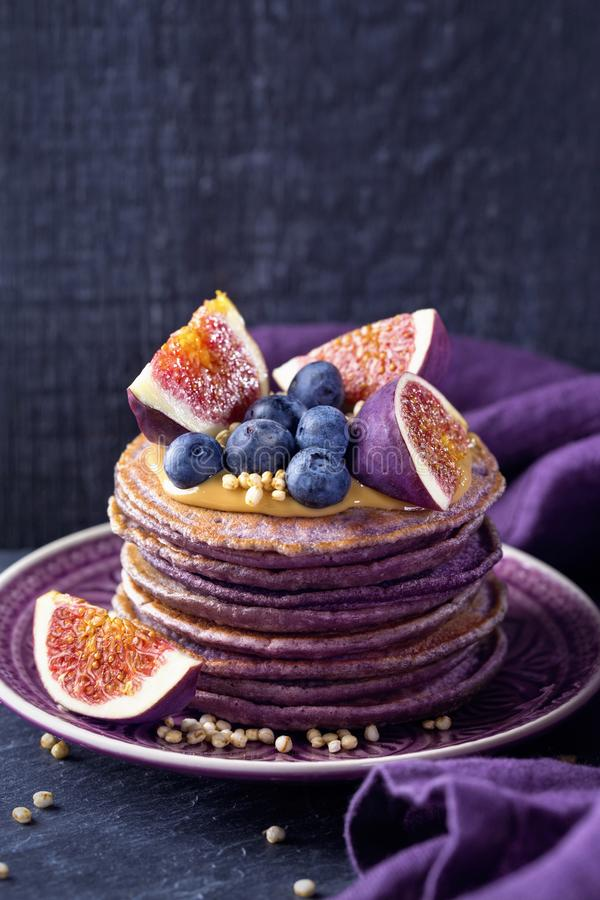 Healthy lilac pancakes. With chokeberry and acai powder topped with peanut butter with figs and blueberries royalty free stock photos