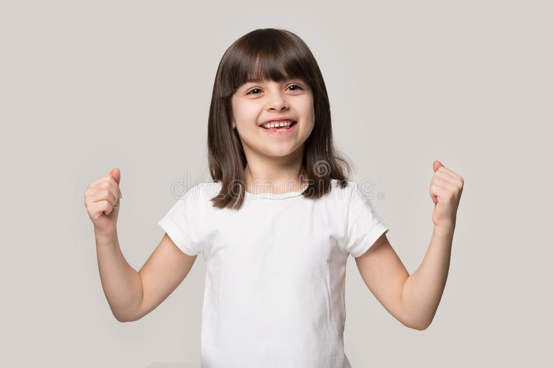 Healthy little girl showing hands biceps strength isolated on beige. Happy strong little girl showing hands bicep strength make fists feels healthy posing stock image
