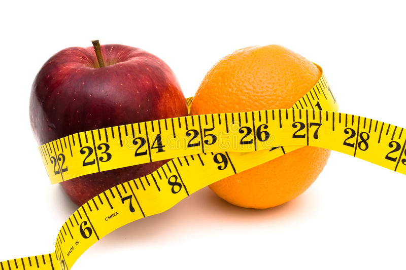 Healthy Living. An apple and an orange with a measuring tape on a white background, healthy living stock images