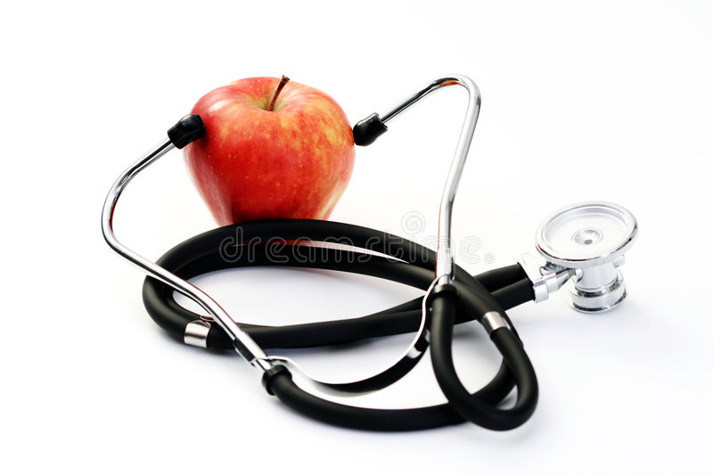 Healthy living. Stethoscope and red apple on white - healthy living stock image