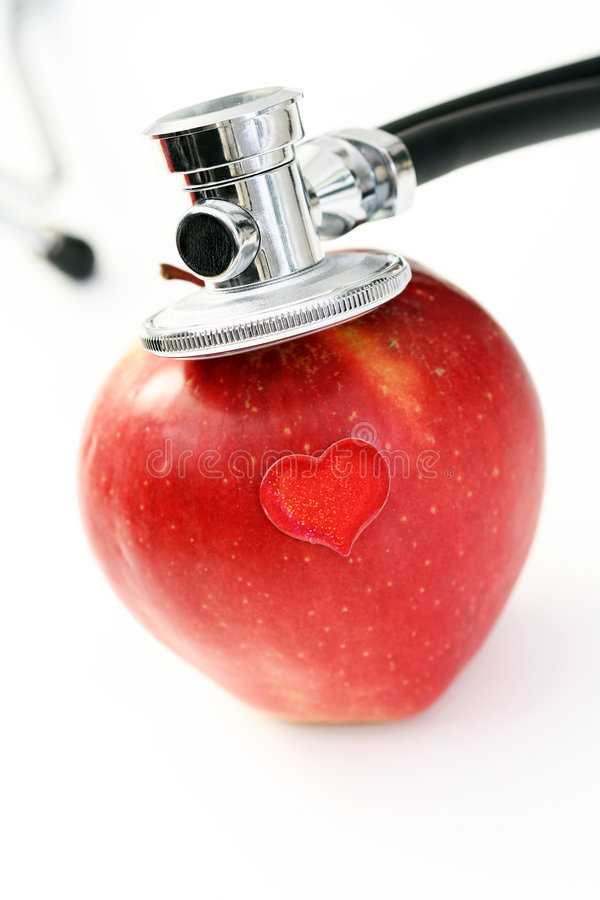 Healthy living. Stethoscope and red apple on white - healthy living royalty free stock photo