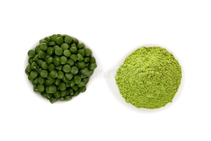Healthy living. Spirulina pills and wheatgrass. stock image