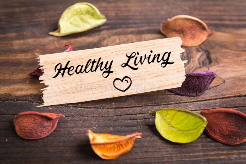 Healthy Living text. In wooden card with dried flower on wood stock images