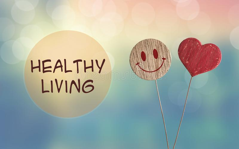Healthy living with heart and smile emoji. Healthy living with wooden heart and smile emoji on bokeh light background royalty free stock photos