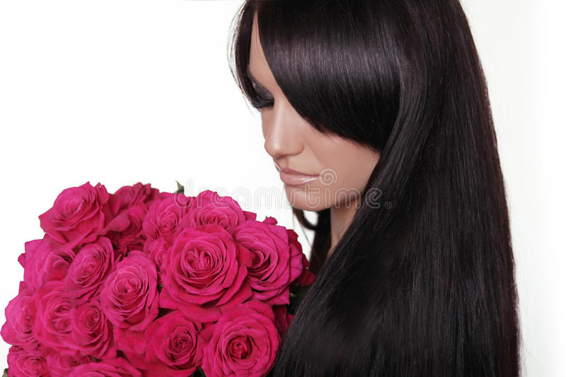 Healthy long hair. Brunette woman with fringe holding pink bouquet of roses isolated on white background. Hairstyle. stock image