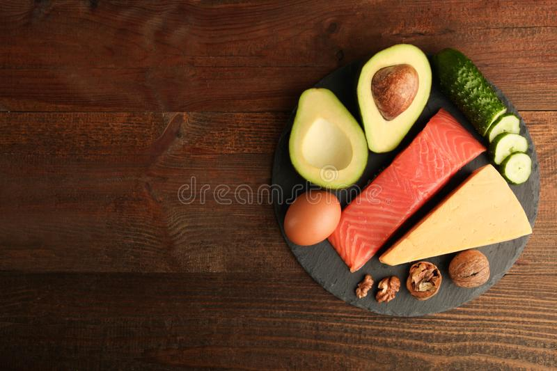 Healthy low carbs products. On slate blackboard on wooden background. Concept ketogenic diet, healthy food. Top view, copy space stock photo