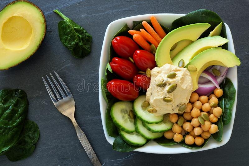 Healthy lunch bowl with super-foods and fresh vegetables. Healthy lunch bowl with super-foods and fresh mixed vegetables, overhead scene on dark slate royalty free stock images