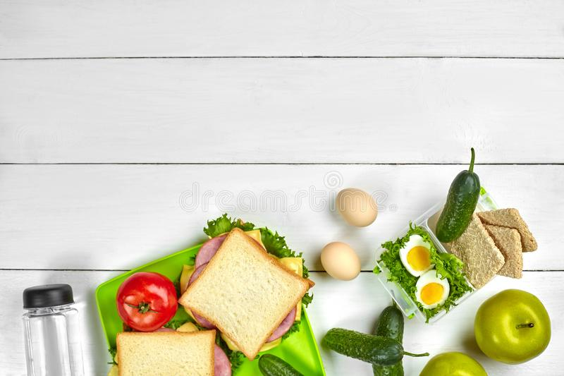 Healthy lunch box with sandwiches, eggs and fresh vegetables, bottle of water on rustic wooden background. Top view with. Copy space. Still life. Flat lay stock photo