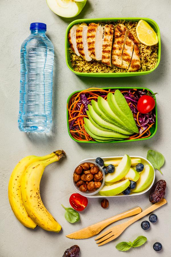 Healthy lunch in boxes. Healthy meal prep containers: Couscous with grilled chicken breast, salad, avocado, berry, apple, nuts and dry dates. Keto, ketogenic royalty free stock image