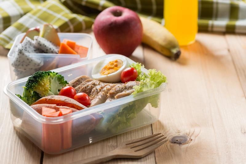 Healthy lunch boxes in plastic package, Grilled chicken breast with sweet potato, egg and vegetable salad, fruit, orange juice. stock images