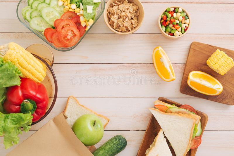 Healthy lunch boxes with sandwich, fresh vegetables, fruits from topview stock photos