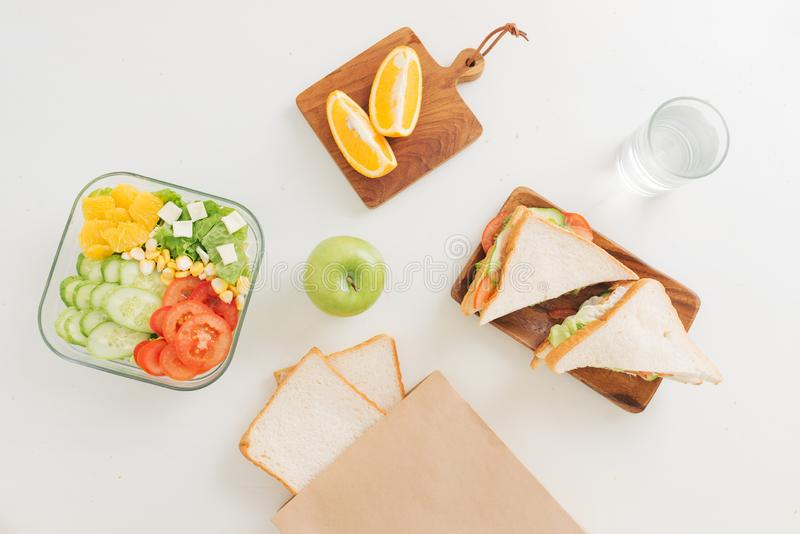Healthy lunch boxes with sandwich, fresh vegetables, fruits from topview stock image