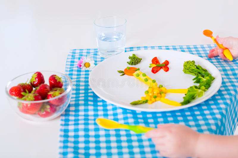 Healthy lunch for children. Healthy vegetarian lunch for little kids. Kid meal. Vegetable and fruit served as animals, corn, broccoli, carrot, strawberry helping stock photo
