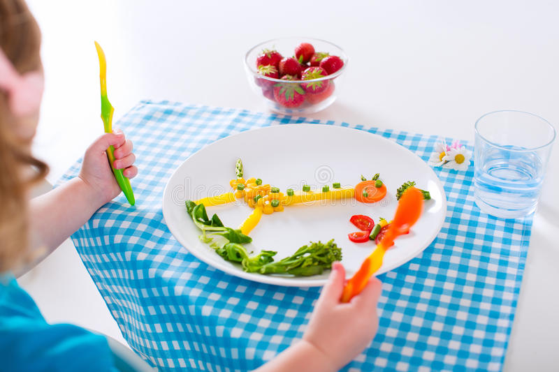 Healthy lunch for children. Healthy vegetarian lunch for little kids. Kid meal. Vegetable and fruit served as animals, corn, broccoli, carrot, strawberry helping royalty free stock photo