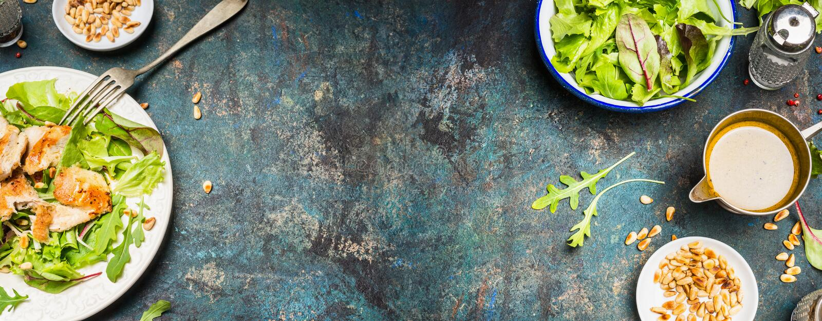 Healthy lunch eating with Chicken salad , pine nuts and oil dressing. Chicken salad with green leaves served on rustic background, top view, place for text stock photography