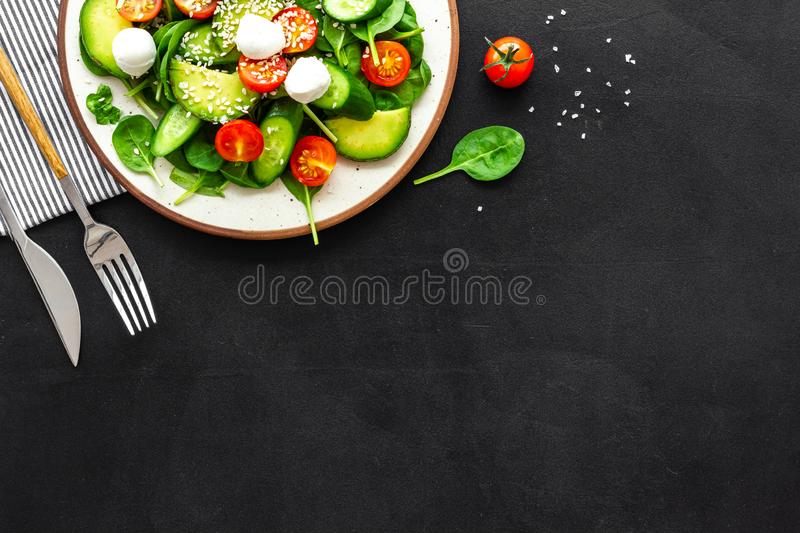 Healthy lunch. Fresh vegetable salad on black background top view copy space royalty free stock photos