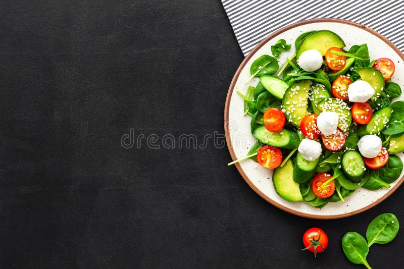 Healthy lunch. Fresh vegetable salad on black background top view copy space royalty free stock photography