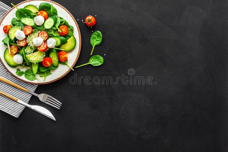 Healthy lunch. Fresh vegetable salad on black background top view copy space stock photography