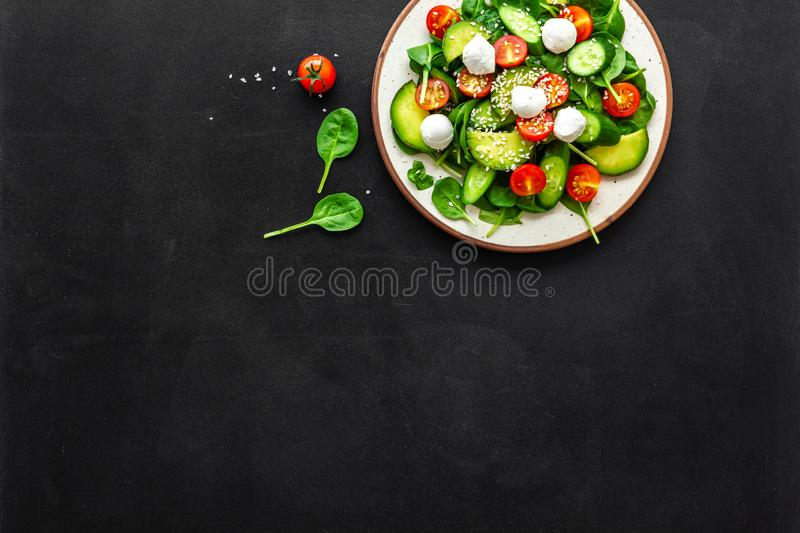Healthy lunch. Fresh vegetable salad on black background top view copy space royalty free stock photo