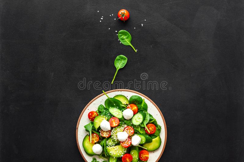 Healthy lunch. Fresh vegetable salad on black background top view space for text royalty free stock images