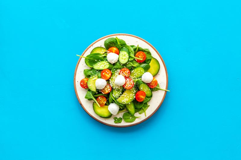 Healthy lunch. Fresh vegetable salad on blue background top view copy space royalty free stock photography