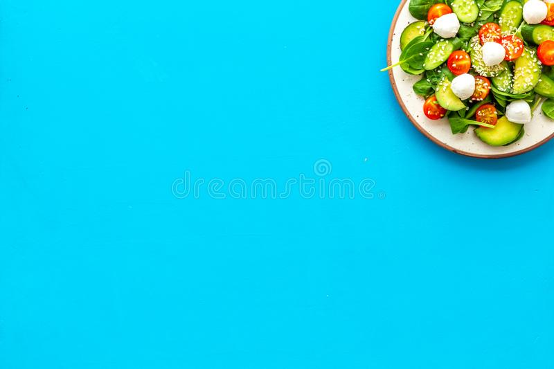 Healthy lunch. Fresh vegetable salad on blue background top view copy space stock photography