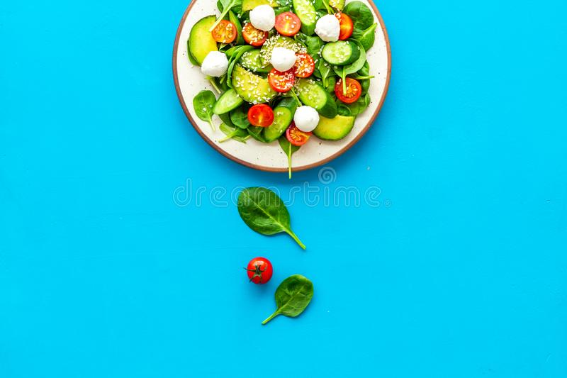 Healthy lunch. Fresh vegetable salad on blue background top view copy space stock photo