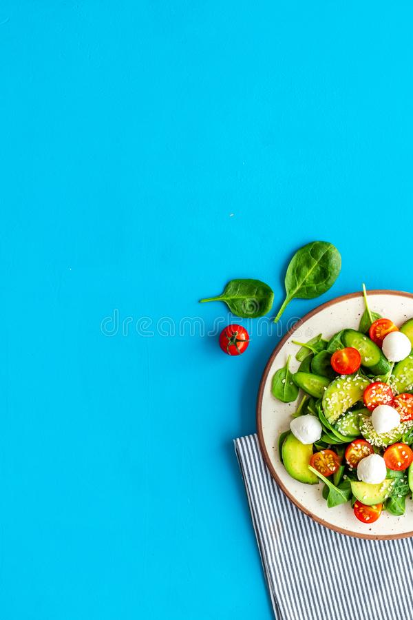 Healthy lunch. Fresh vegetable salad on blue background top view space for text stock photo