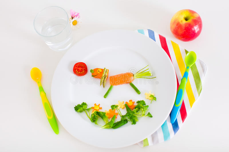 Healthy lunch for kids. Healthy vegetarian lunch for little kids, vegetables and fruit served as animals, corn, broccoli, carrots and fresh strawberry helping royalty free stock images