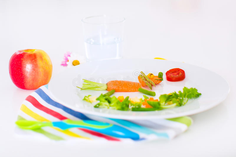 Healthy lunch for kids. Healthy vegetarian lunch for little kids, vegetables and fruit served as animals, corn, broccoli, carrots and fresh strawberry helping royalty free stock photo