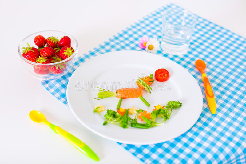 Healthy lunch for little kids. Healthy vegetarian lunch for little kids, vegetables and fruit served as animals, corn, broccoli, carrots and fresh strawberry royalty free stock photos