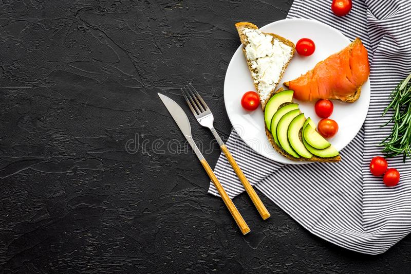 Healthy lunch with mini sandwiches cheese, fish and avocado on black background top view space for text stock images