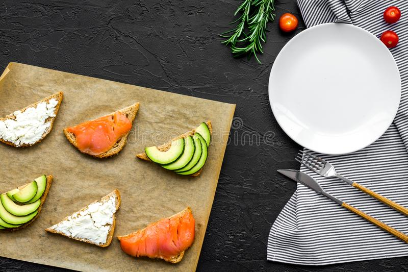 Healthy lunch with mini sandwiches cheese, fish and avocado on black background top view space for text royalty free stock photography