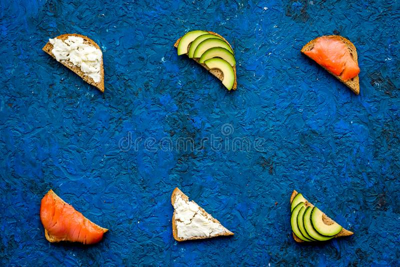 Healthy lunch with mini sandwiches cheese, fish and avocado on blue background top view space for text stock photos