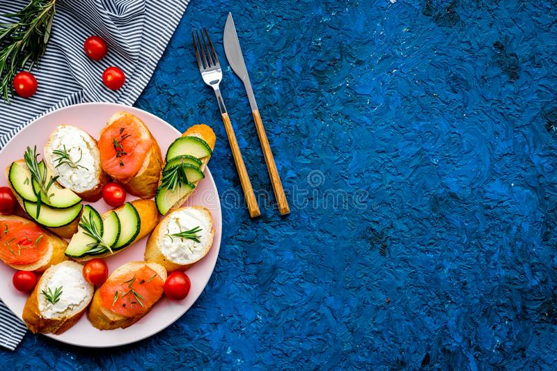 Healthy lunch with mini sandwiches cheese, fish and avocado on blue background top view space for text stock photography
