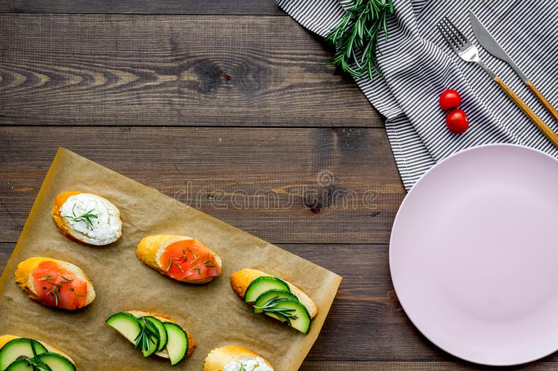 Healthy lunch with mini sandwiches cheese, fish and avocado on wooden background top view space for text stock photography