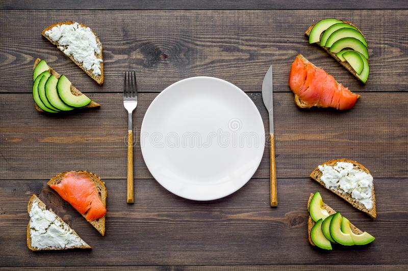 Healthy lunch with mini sandwiches cheese, fish and avocado on wooden background top view space for text royalty free stock images