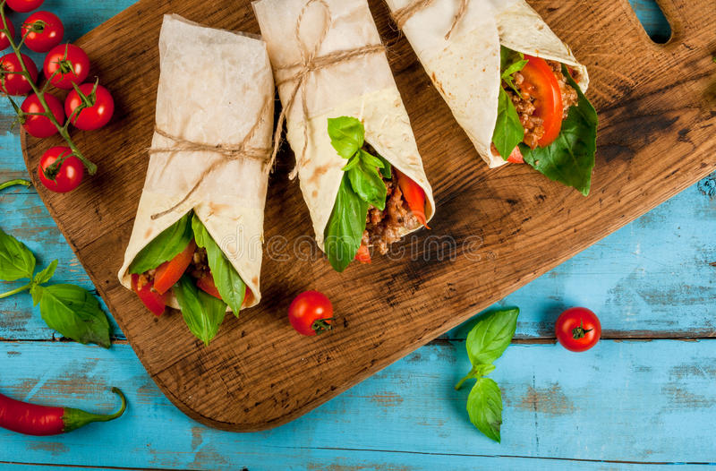 Healthy lunch snack. Sandwiches twisted roll Tortilla with beef. And vegetables a wooden cutting board on blue wooden rustic table, copy space, top view stock images